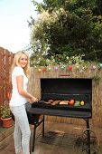 image of braai  - Attractive young woman cooking on a gas barbecue outdoors on a garden patio with meat and vegetables - JPG