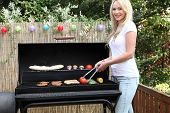 stock photo of braai  - Beautiful blond woman barbecuing on a patio standing in front of a gas fire cooking fresh vegetables and meat - JPG