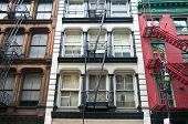 picture of duplex  - Three colorful red brown and white apartment buildings facades with emergency escapes - JPG