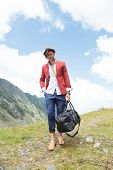 full length picture of a young fashion man walking in the mountains with a bag in his hand while loo