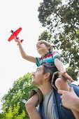 stock photo of aeroplane  - Low angle view of a boy with toy aeroplane sitting on father - JPG