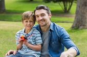 stock photo of aeroplane  - Portrait of a young boy with toy aeroplane sitting on father - JPG