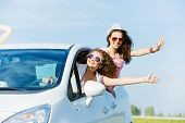 image of car-window  - Young pretty women leaning out of car window - JPG