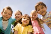 stock photo of preschool  - Portrait of smart preschoolers embracing each other on background blue sky - JPG