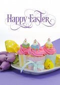 stock photo of hen party  - Happy Easter pink yellow and blue cupcakes with cute chicken decorations and tulips on purple background for children party or holiday treat with beautiful sample text or copy space for your text here - JPG