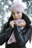 image of cold-weather  - nice girl in winter day outside in park dressing leather jacket and pink scarf and hat - JPG
