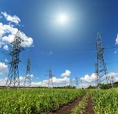 image of mast  - landscape with electric masts and road in green field - JPG