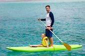 stock photo of paddling  - Father and his adorable little daughter paddling on stand up board having fun during summer beach vacation - JPG