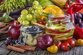 stock photo of pickled vegetables  - canned pepper and pear with autumn fruits and vegetables around - JPG