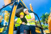 stock photo of machinery  - Asian construction machinery driver discussing with foreman blueprints  or tablet computer of building site  - JPG