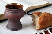 stock photo of communion  - Chalice with red wine bread and Holy Bible on a tablecloth - JPG