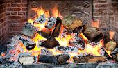 stock photo of fiery  - Glowing coals in a wood fire with fiery orange flames in a brick hearth or fireplace with a wrought iron backplate - JPG
