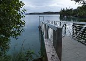 image of dock  - A silver metal dock leads to the water of the Kachemak Bay - JPG
