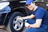 picture of gun shop  - Smiling mechanic inflating a tire - JPG
