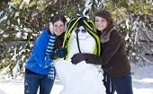 Two Teenage Girls With Snowman