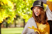 picture of fall day  - Young woman with autumn leaves in hand and fall yellow maple park  background  - JPG