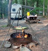 stock photo of trailer park  - An outdoor grill at a Pennsylvania State Park with a picnic table and camping trailer in the background - JPG