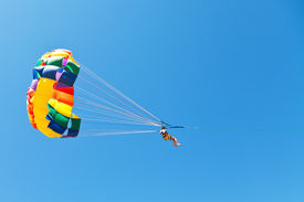 pic of parasailing  - woman parasailing on parachute in blue sky in summer day - JPG
