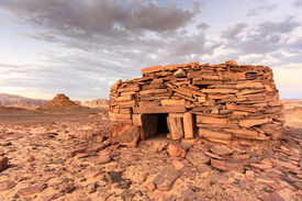 stock photo of empty tomb  - Ancient tombs in the desert glow orange in the late evening sun - JPG