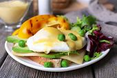 image of benediction  - Toast with egg Benedict and avocado on plate on wooden table - JPG