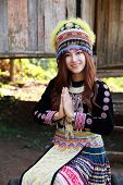 foto of hmong  - Traditionally dressed Mhong hill tribe woman pay respect at the wooden cottage - JPG