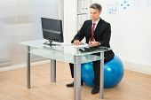 picture of pilates  - Businessman Writing On Paper Sitting On Pilates Ball In Office - JPG