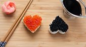 pic of soy sauce  - Two heart shaped sushi with salmon roe and beluga caviar on wooden desk - JPG