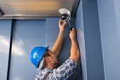 stock photo of cctv  - Photo Of Professional Cctv Technician Adjusting Cctv Camera - JPG