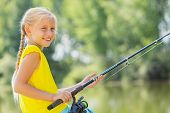 pic of  preteen girls  - Portrait of cute girl sitting at bank and fishing - JPG