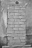 pic of oddities  - Bricked up door and weathered wall of an abandoned building - JPG