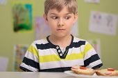 foto of schoolboys  - Unhappy schoolboy with healthy breakfast at school - JPG