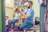stock photo of father daughter  - Young father styling hair of his daughter - JPG