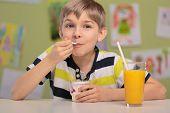 stock photo of school lunch  - Happy boy eating healthy lunch at school - JPG