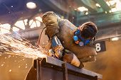 image of goggles  - Young man with protective goggles welding in a factory - JPG