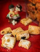 picture of baked raisin cookies  - Traditional mini cookies as a gift with raisin strewed icing sugar on a red background - JPG