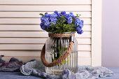 foto of blue-bell  - Blue bell flowers in glass vase on wooden background - JPG