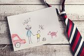 foto of composition  - Fathers day composition with childs drawing and colorful tie laid on wooden desk backround - JPG