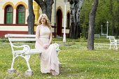 stock photo of evening gown  - Beautiful blond curly woman wearing evening peach color gown sitting on white bench outdoors - JPG