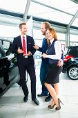 pic of showrooms  - Seller or car salesman and clients or customers in car dealership presenting the interior decoration of new and used cars in the showroom - JPG