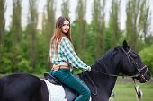 stock photo of horse girl  - beautiful girl riding a horse - JPG