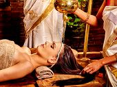 picture of massage oil  - Young woman having oil Ayurveda spa treatment - JPG