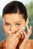 pic of contact lenses  - Woman applying contact lens in her eye - JPG