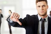stock photo of disappointed  - Disappointed young business man with thumb down - JPG