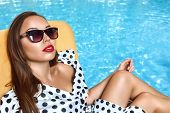stock photo of sun-tanned  - Portrait of young beautiful woman in sun glasses with perfect tanned skin - JPG