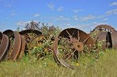 pic of junk-yard  - Huge industrial and steam engine wheels are piled in a salvage yard  - JPG