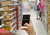 stock photo of supermarket  - a shopper using mobile phone in supermarket - JPG