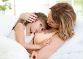 picture of cuddle  - Mother Cuddling Daughter Child At Home In Bedroom - JPG