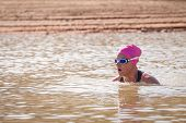 pic of swimming  - An active female is seen swimming across a dam while wearing a pink swimming cap - JPG
