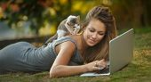 stock photo of kitty  - Beautiful girl with her kitty and laptop outdoors - JPG