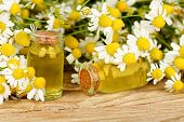 foto of chamomile  - homeopathy concept with bottles and chamomile flowers on wood - JPG